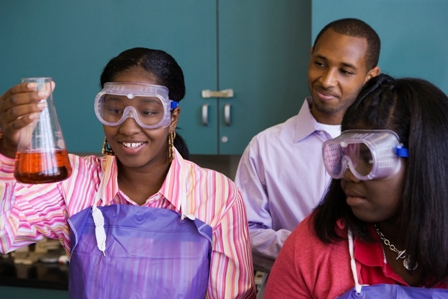 African teenage girl examining experiment in chemistry lab