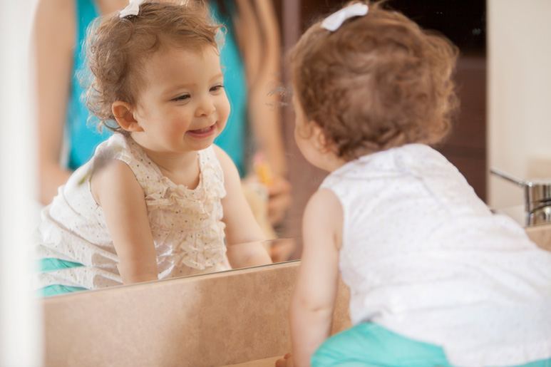 Baby girl seeing herself in mirror