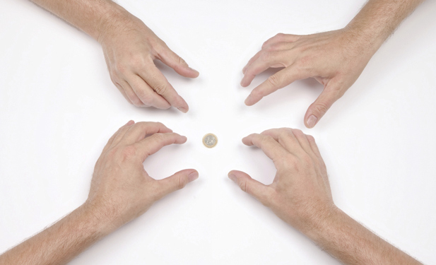 Four hands reaching for coin