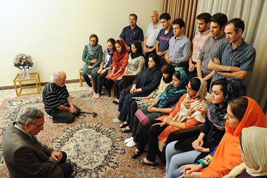 Muhammad Nourizad, a former journalist and Muhammad Maleki, the first head of Tehran University following the Islamic Revolution, are seen on their knees in humility before a group of Baha'i students