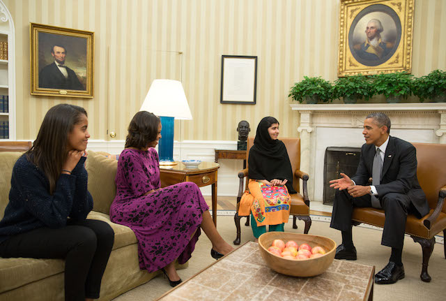 President Barack Obama, First Lady Michelle Obama, and their daughter Malia meet with Malala Yousafzai, the young Pakistani schoolgirl who was shot in the head by the Taliban a year ago, in the Oval Office, Oct. 11, 2013.