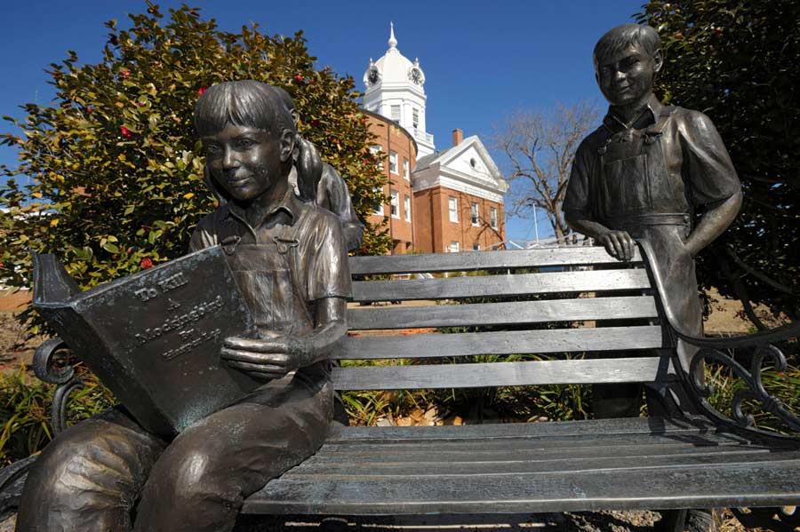"A bronze statue of a young girl reading ""To Kill a Mockingbird,"" in Monroeville, Alabama. Photograph by G. M. Andrews"