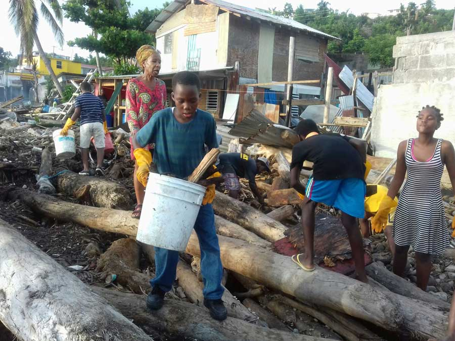 Neighbors in the Newtown neighborhood of Roseau help clear the bay of debris following the destruction left by the hurricane.