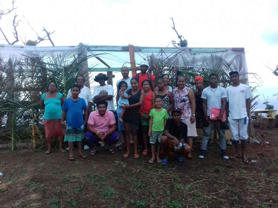 Friends and neighbors gather in front of a greenhouse they constructed together. The community in this part of the remote Kalinago territory has begun to hold classes for children and young adolescents on the site, as well as prayer gatherings open to all.