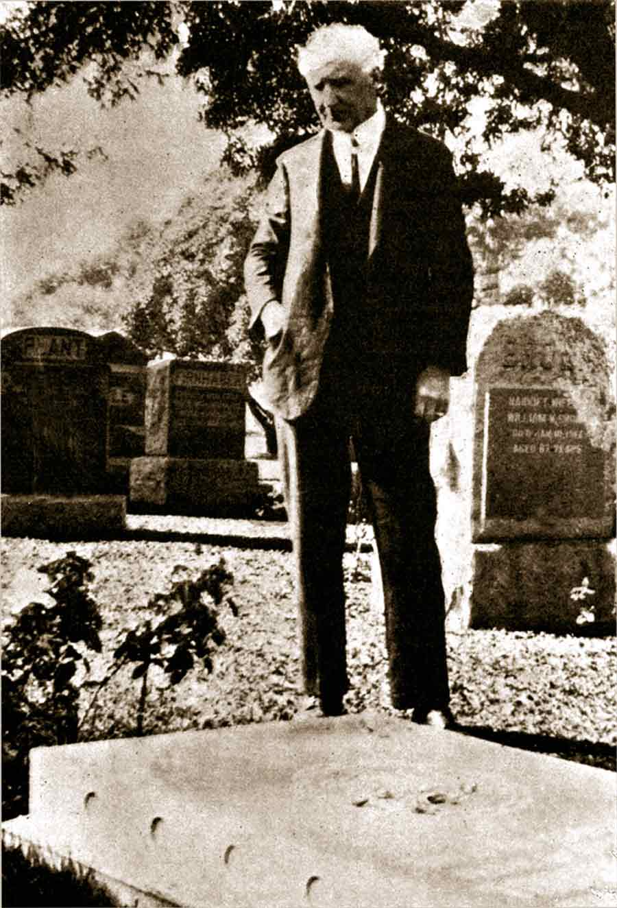 """Howard MacNutt stands at the grave, in Los Angeles cemetery, of Thornton Chase, another disciple of 'Abdu'l-Baha, who was designated by 'Abdu'l-Baha as """"the first American believer."""""""