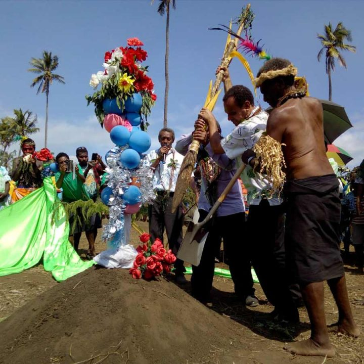Foreign Minister Ralph Regenvanu and President of the Malvatumauri National Council of Chiefs Willie Plasua together drive the kakel—a traditional wooden spade—into the soil, symbolizing the start of construction on the local Baha'i House of Worship on the island of Tanna, Vanuatu.
