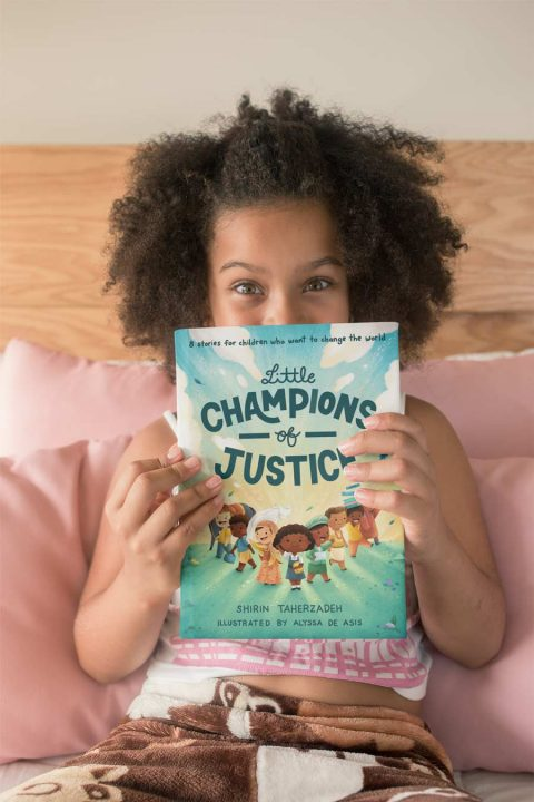 Little girl reading Little Champions of Justice.