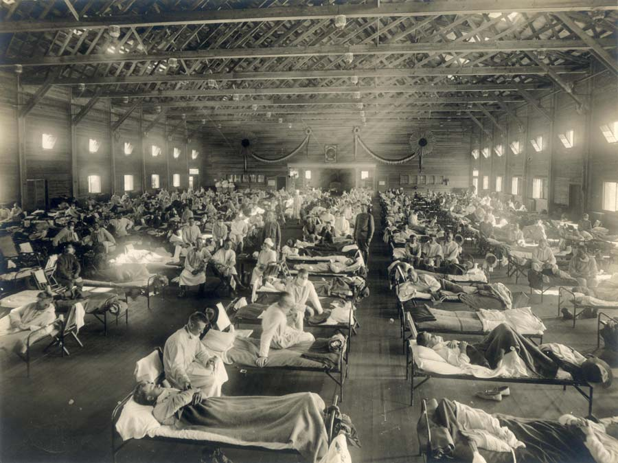 Beds with patients in an emergency hospital in Kansas, in the midst of the Spanish flu epidemic. The flu struck while America was at war, and was transported across the Atlantic on troop ships (1918).