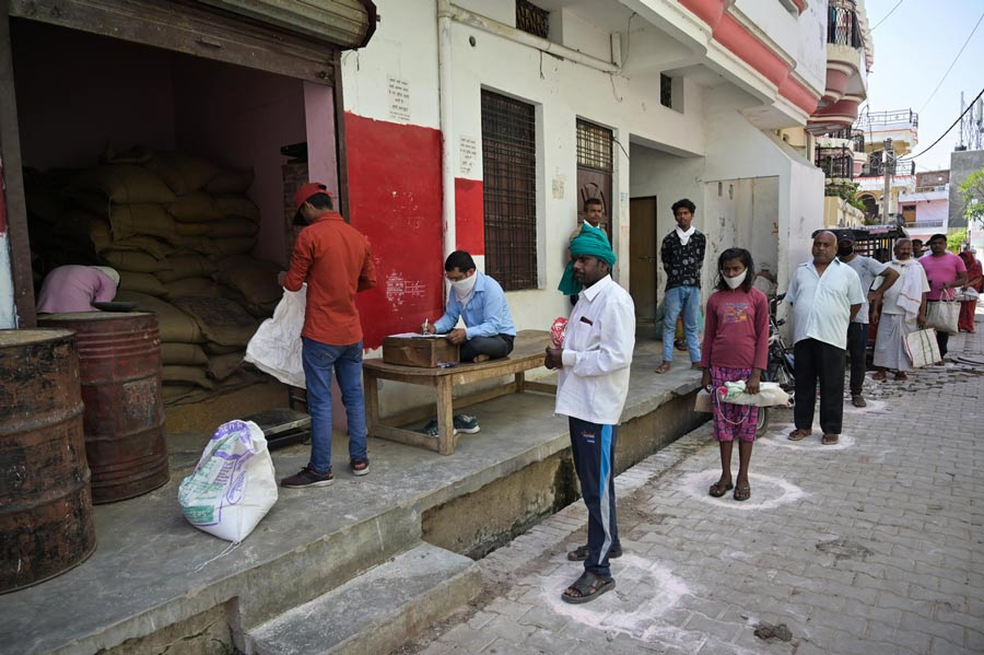 People maintain social distance as they in queue to receive free ration during lockdown in wake of Coronavirus pandemic in Prayagraj on Thursday, April 02, 2020.