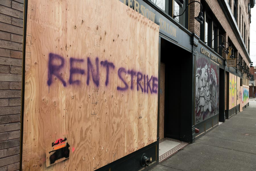 Seattle, USA – March 31, 2020: A boarded up business with 'rent strike' painted on it.