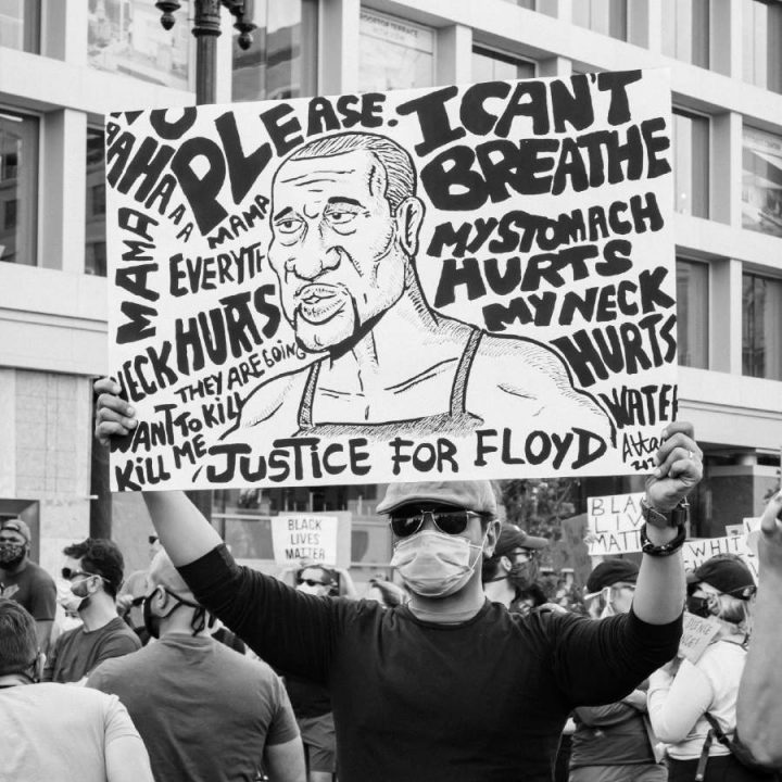 A man holding up a poster in honor of George Floyd.