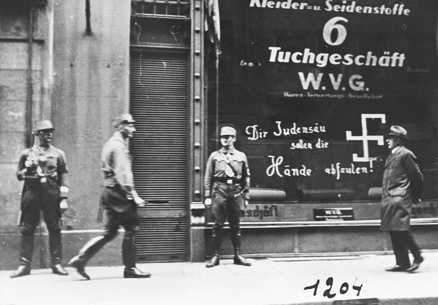 """More than 50 years after Baha'u'llah's passing Nazi storm troopers are seen guarding a Jewish-owned business in Vienna shortly after the Anschluss. The graffito on the store window reads, """"You Jewish pig, may your hands rot off!"""""""