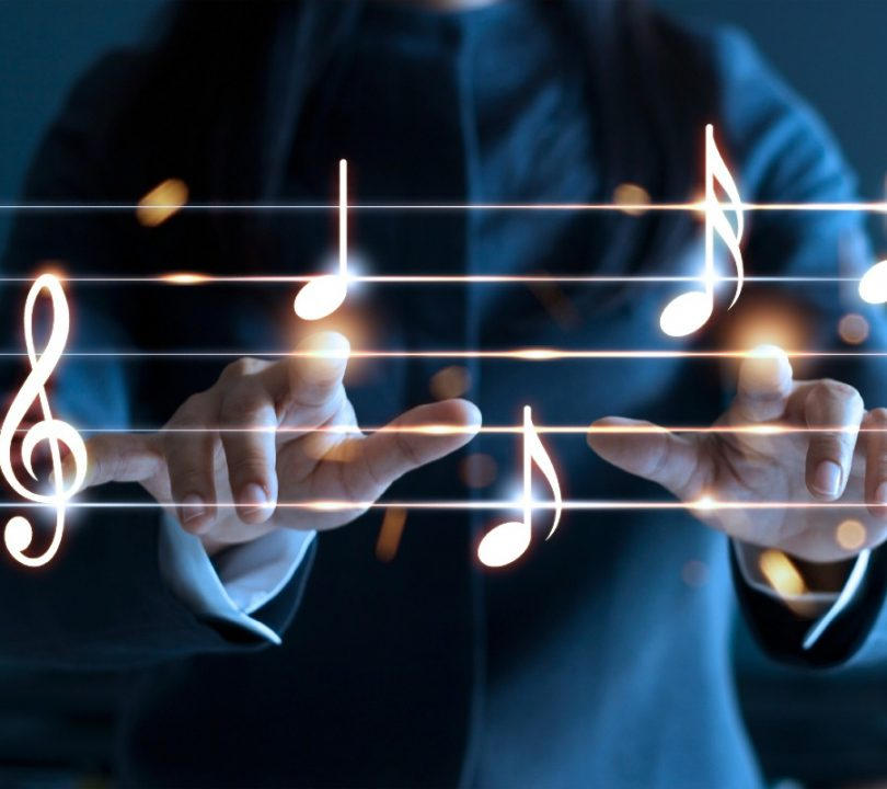 A musician pointing to musical notes in the air