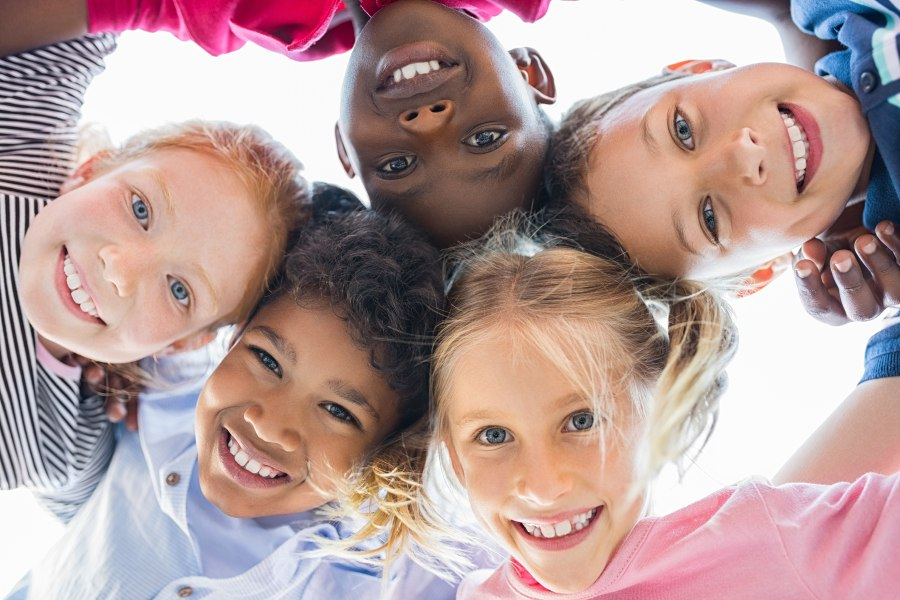 A group of diverse children hugging