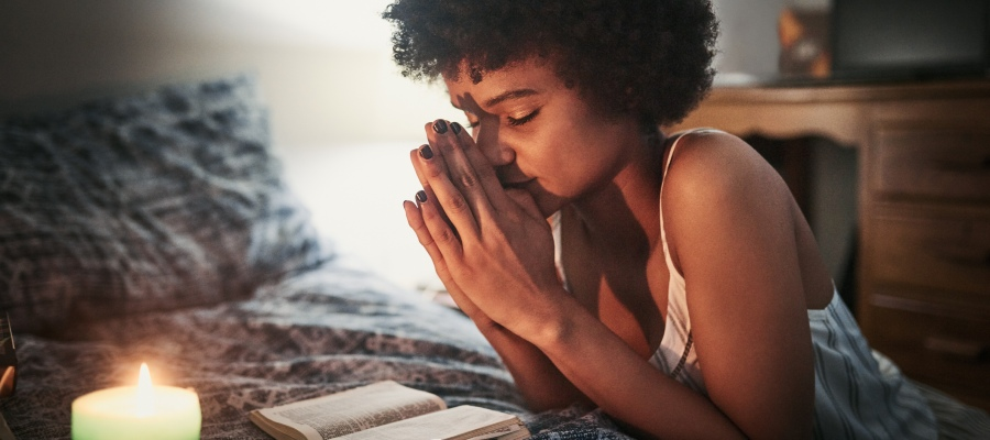 a woman praying near candlelight before bed