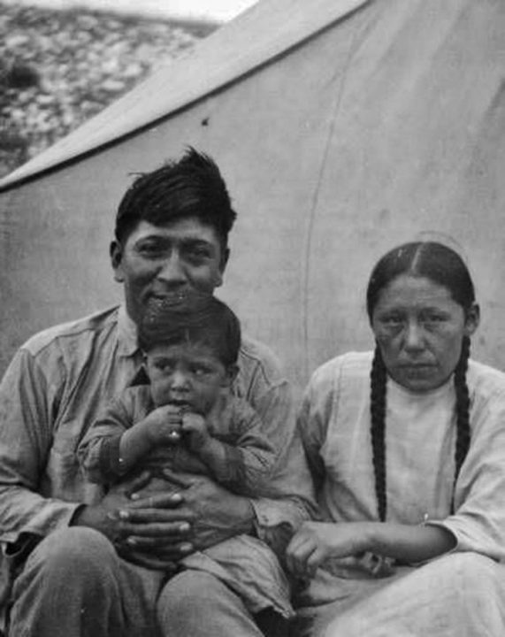 John Stands in Timber (L) with his wife and son (1926).