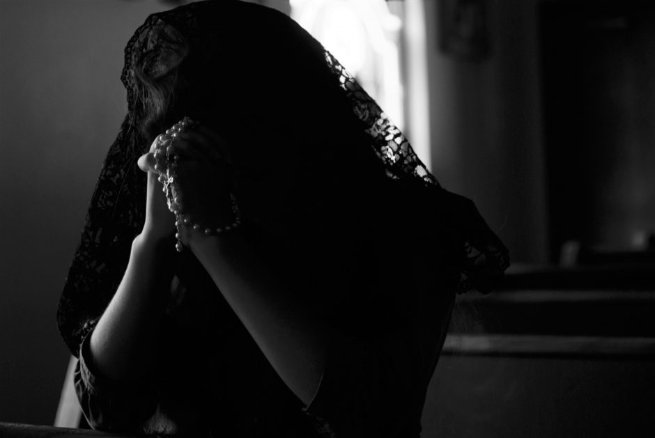A woman grieving and praying