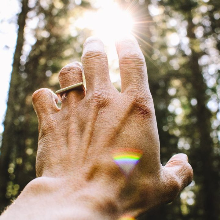 An image of a man reaching up to the sunlight