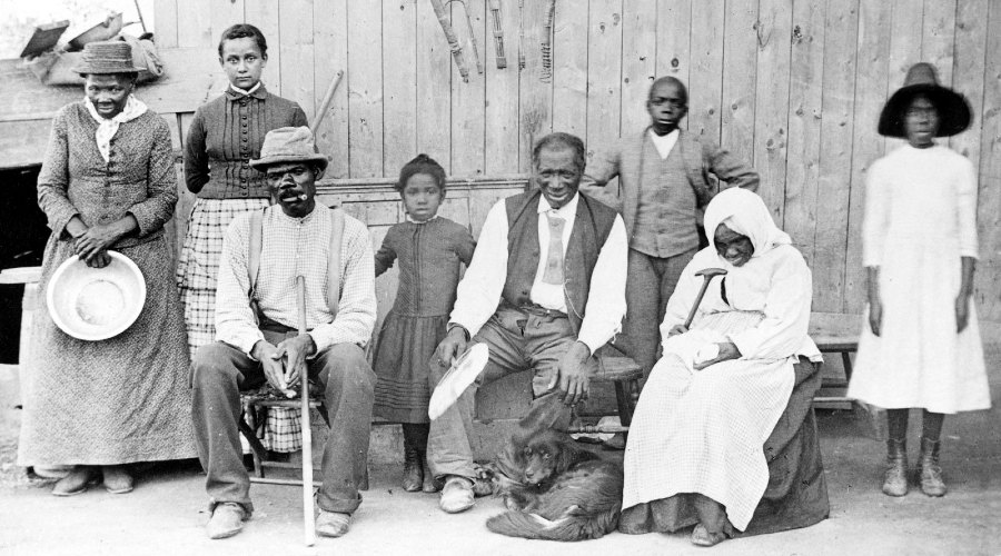 Harriet Tubman in 1887 (far left), with her husband Nelson Davis (seated, with cane), their adopted daughter Gertie (beside Harriet), and other family members, neighbors, and elderly boarders at her home in Auburn, New York