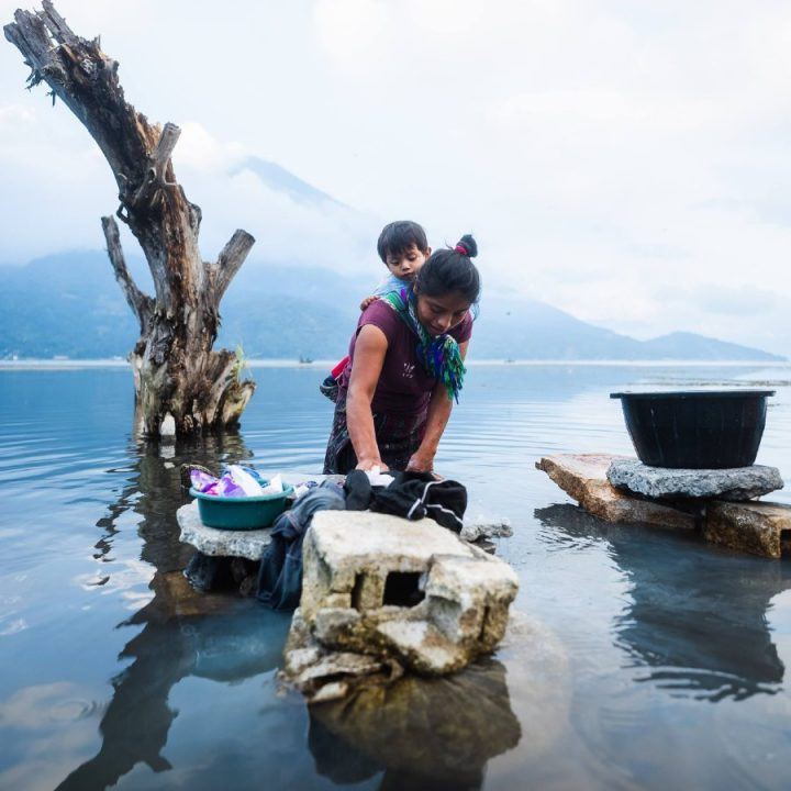 Young woman holding young child on her back as she washes clothes in a lake